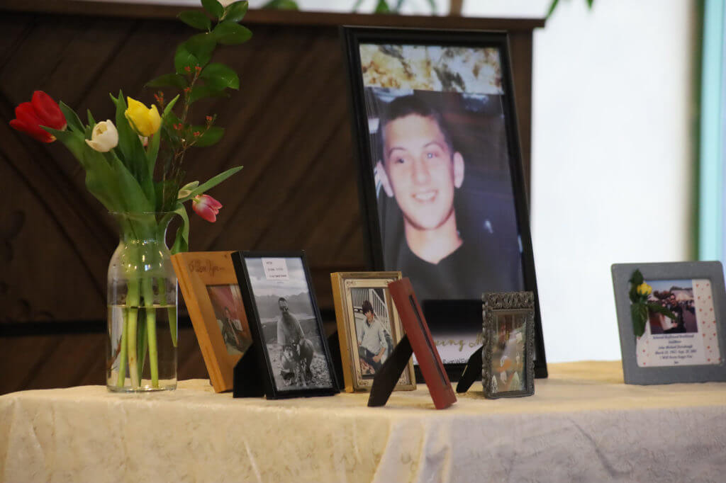 A memorial table with framed photos and a vase of flowers.