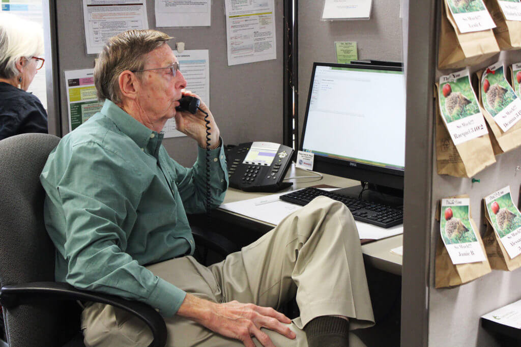 An older man talking on the phone in front of his computer.