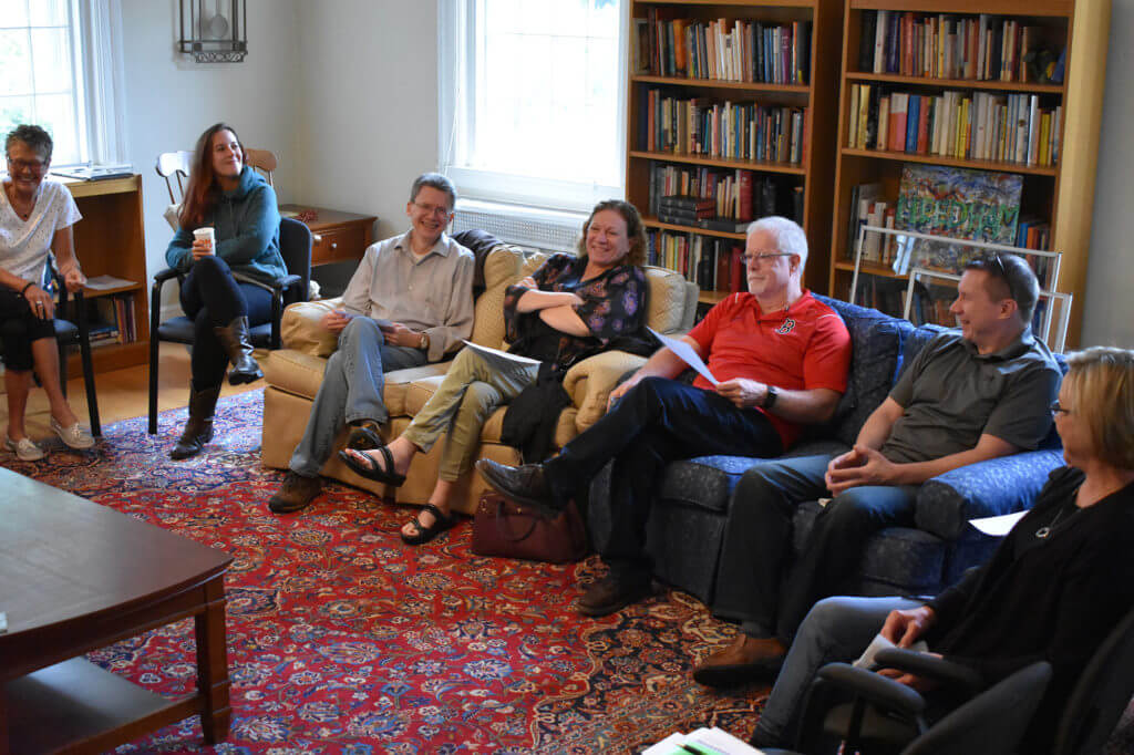 A group of people sitting in a living room together.