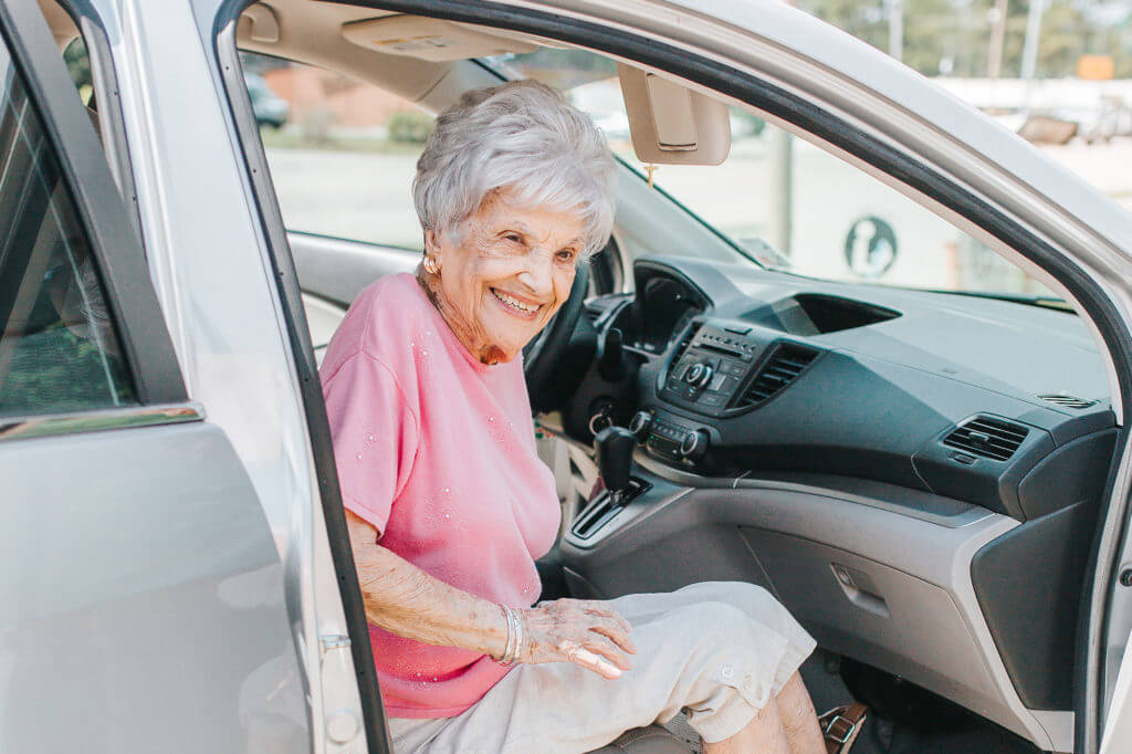 An elderly woman sitting in the passenger seat of a car.