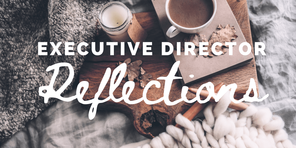 "cozy scene with blanket, candle, hot chocolate behind the words ""Executive Director Reflections"""