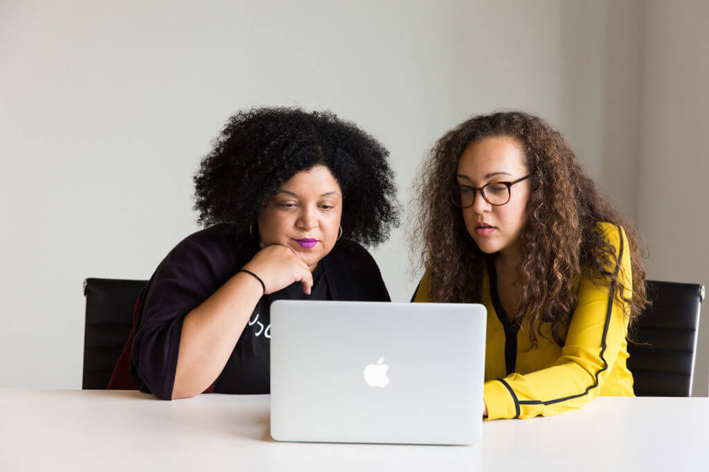 Two women sitting at a desk with an Apple laptop.