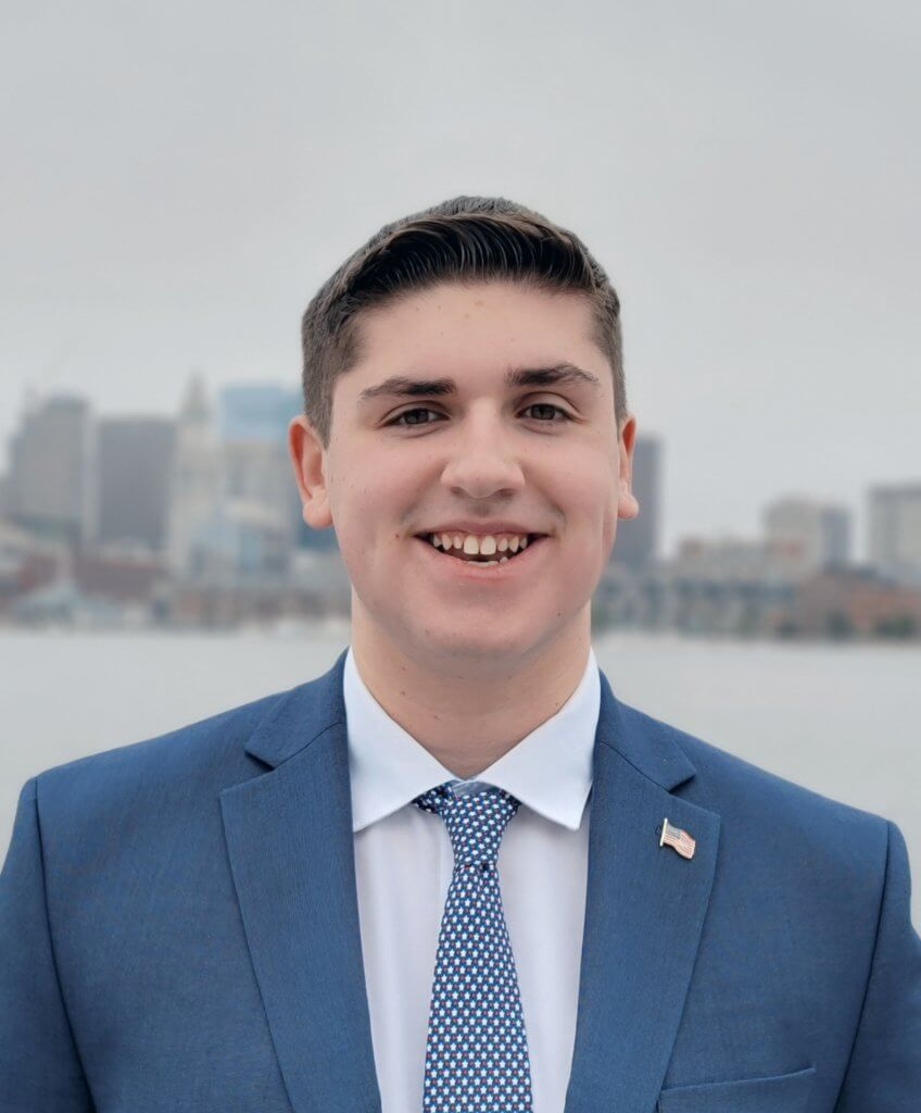 person in suit outside with boston skyline behind them