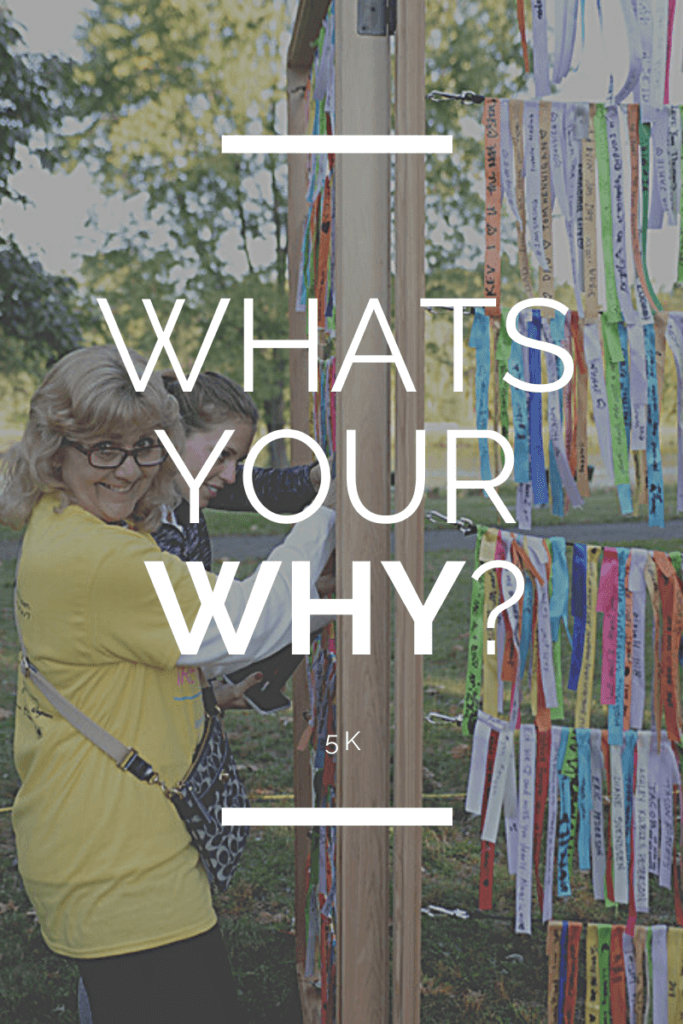 Woman standing in the background of the text. She is smiling.   Text overlays: Whats Your Why? 5K